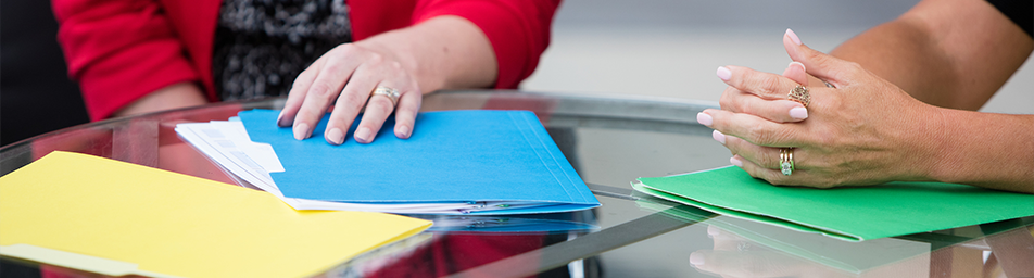 hands of two women with multi-colored file folders