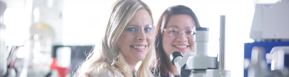 two scientists wearing safety glasses and smiling