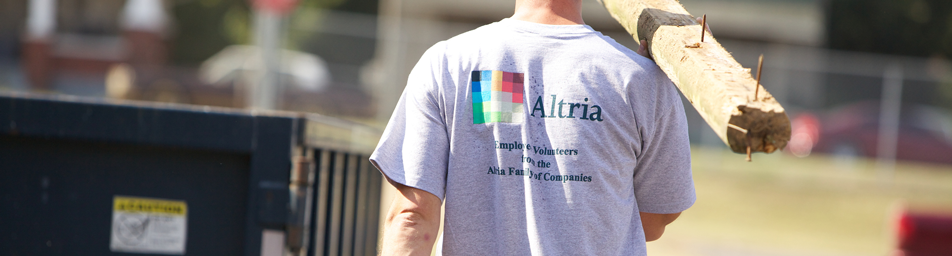 altria volunteer carrying waste to container