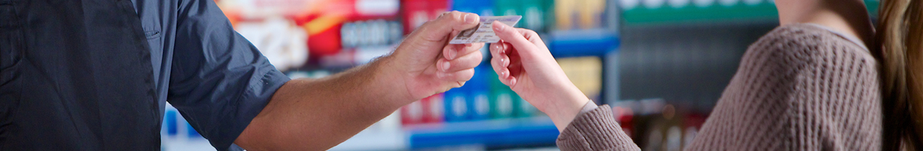 detail of adult consumer handing id to cashier