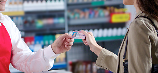 detail of customer showing id to cashier at convenience store