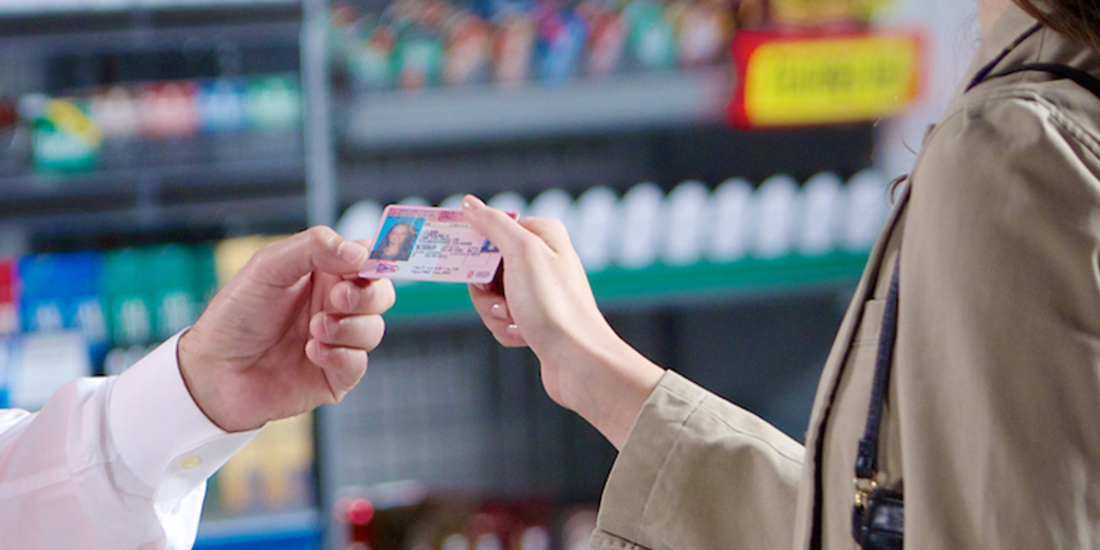 detail of customer handing id to convenience store clerk